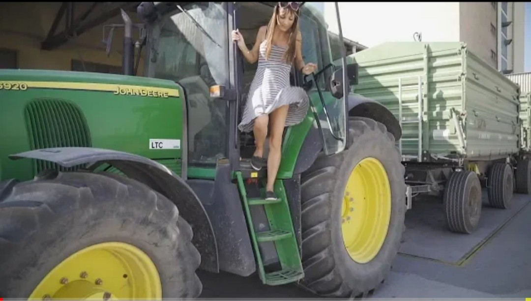 Farmer girl takes the harvest with the John Deere to the warehouse