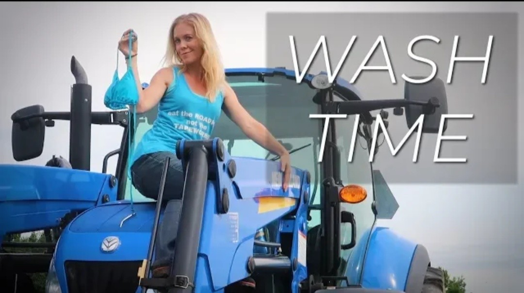Farm Girl Washing the New Holland Tractor in a
